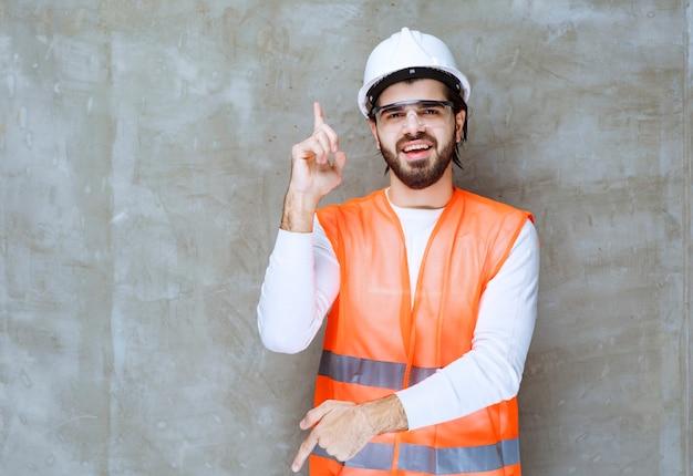 Uomo dell'ingegnere in casco bianco e occhiali protettivi rivolti verso l'alto e verso il basso.