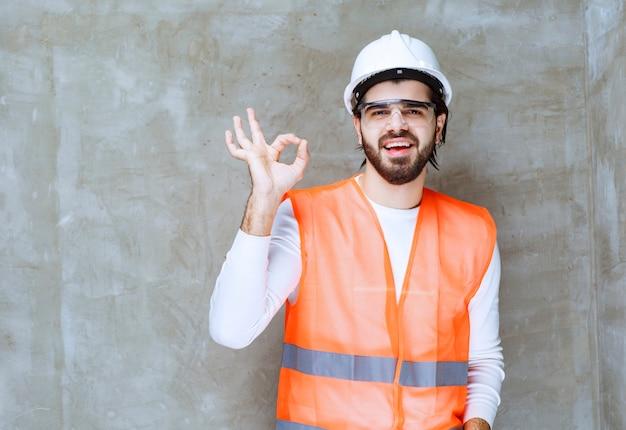 Uomo dell'ingegnere in casco bianco e occhiali protettivi che mostrano il segno giusto della mano.