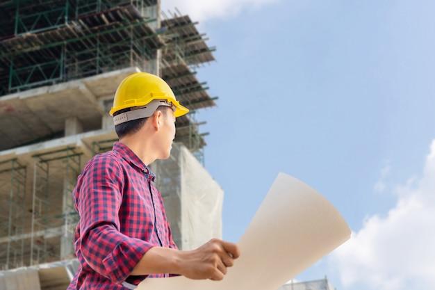 クリッピングパスのチェックと建設現場での計画プロジェクトを持つエンジニア男、青写真を押しながら空を見る男