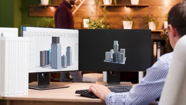 デジタル会社のソフトウェアを使用してコンピューター上の建築物のプロトタイプで働くエンジニアの男。創造性プロジェクトのための産業建設構造を開発する働き者の建築家