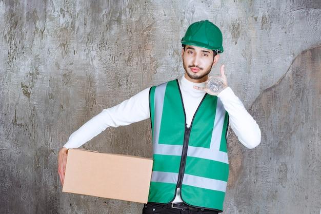Uomo dell'ingegnere in uniforme gialla e casco che tiene un pacco di cartone e chiede una chiamata.