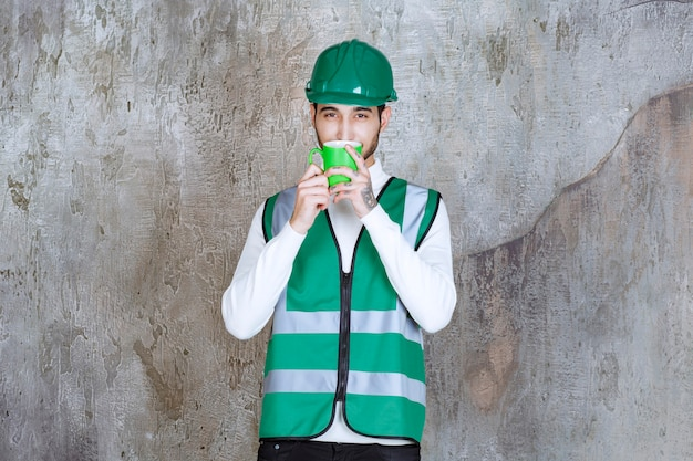 Ingegnere in uniforme gialla e casco con in mano una tazza da caffè verde e annusare il prodotto.