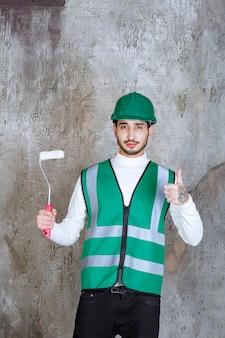 Ingegnere in uniforme gialla e casco che tiene un rullo di rivestimento per la pittura murale e mostra un segno positivo della mano