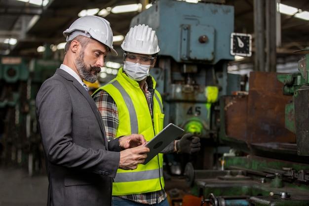 Инженер-менеджер и команда заводских рабочих проверяют машину на производственной линии. концепция совместной работы.