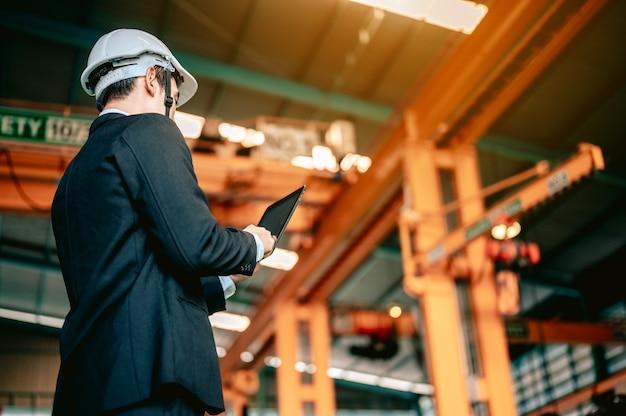 엔지니어 관리자는 선반 기계 로봇 손을 사용하기 위해 태블릿 및 명령 작업자의 설명서를 확인합니다.