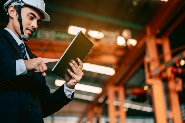 エンジニアマネージャーはタブレットのマニュアルをチェックし、コマンドワーカーは旋盤機械ロボットの手を使用します