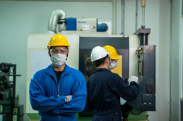Engineer mechanic wearing protective mask working in factory.