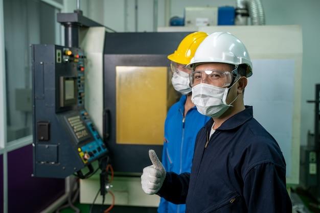 Инженер-механик в защитной маске работает на крупном промышленном предприятии.