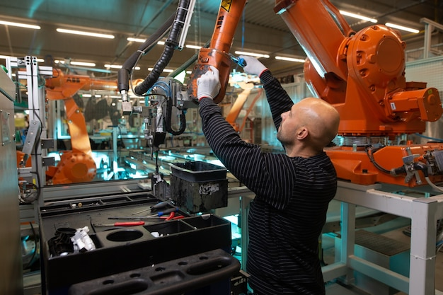 Engineer optimizing production by robotic arm in automotive smart factory, employee in industry, industrial concept