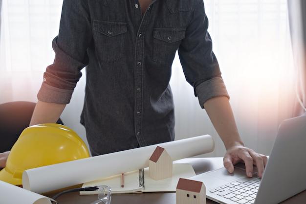 コンピューターのラップトップを使用してオフィスの机の上の建設の青写真と建設設計のためのエンジニアまたは建築家。