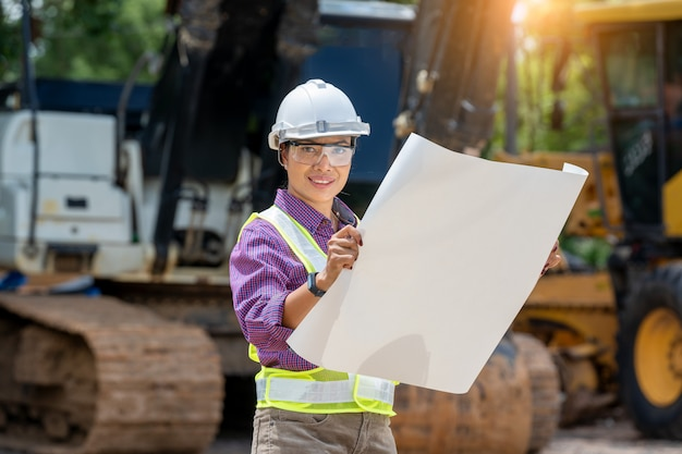 建設現場でローダートラックで青写真を保持しているエンジニアまたは建築家の女性、作業エリアでの建設車両のエンジニアリング。
