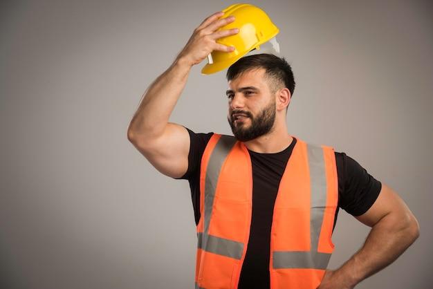 Ingegnere in uniforme arancione che indossa il casco giallo.