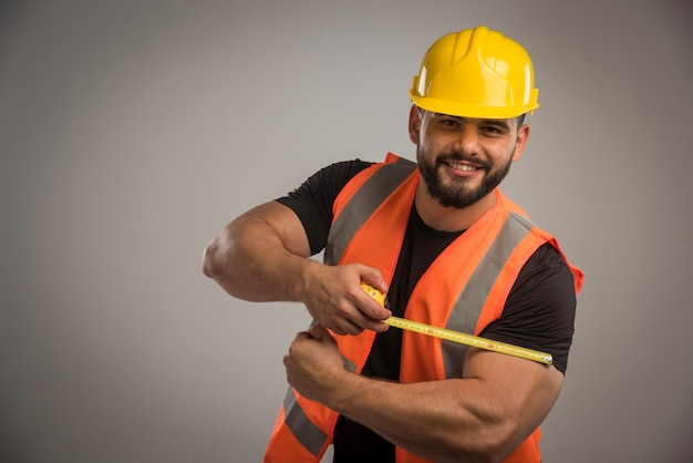Engineer in orange uniform and yellow helmet using ruler.
