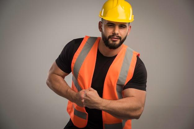 Ingegnere in uniforme arancione e casco giallo con grandi muscoli.