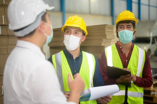Инженеры в защитных масках, работающих на складе Premium Фотографии