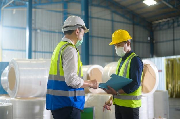 Инженеры в защитных масках, работающих на складе