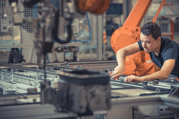 Engineer performs maintenance of industrial robot in a factory