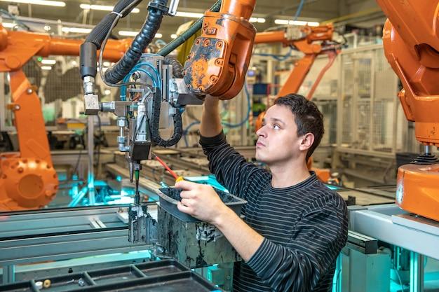 エンジニアは工場で産業用ロボットのメンテナンスを行います