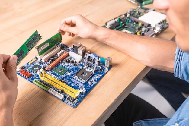 Engineer putting the ram memory module in motherboard