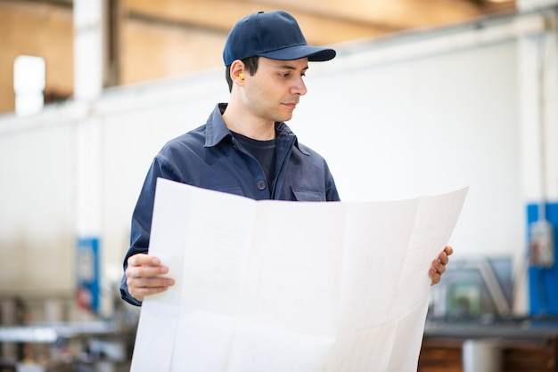 Engineer reading a bluepring drawing in a industrial facility