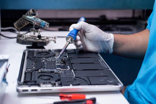 Инженер ремонтирует ноутбук и материнскую плату.