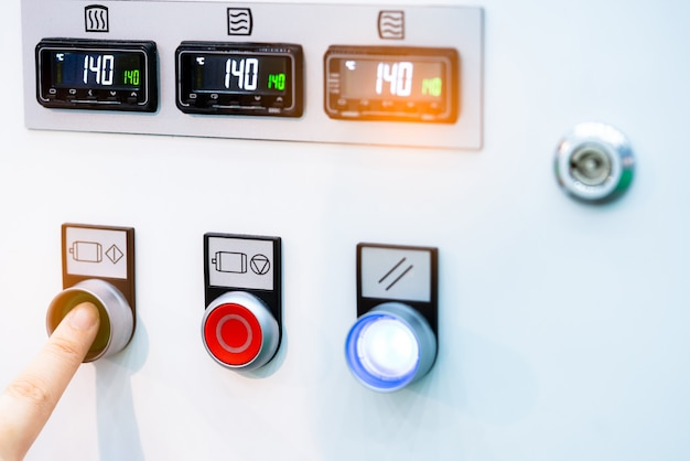 Engineer's hand push green button to open temperature control machine.