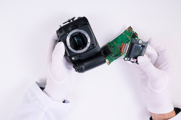Engineer's hands repairing the camera in laboratory. professional camera and lens maintenance support by engineer.