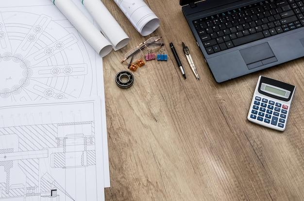 Рабочее место инженера с различными деталями на деревянном столе