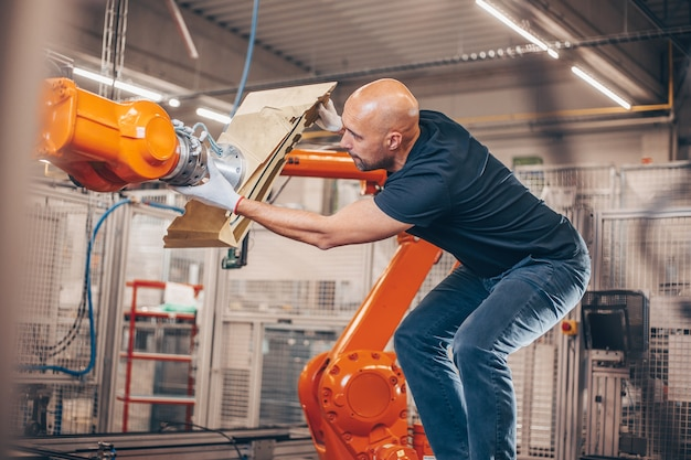 Engineer setting up automatic robot arm for production in automotive, industry factor