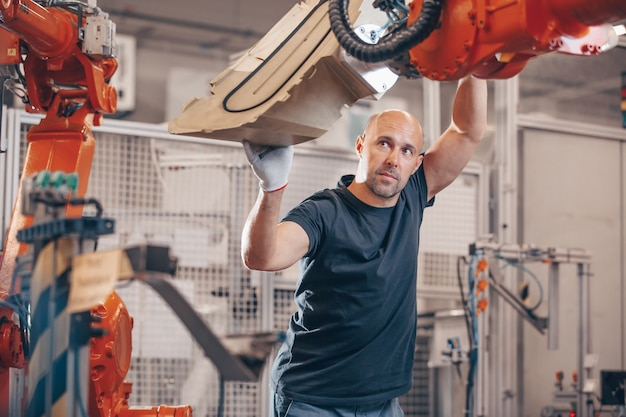 Engineer setting up automatic robot arm for production in automotive, industry factory
