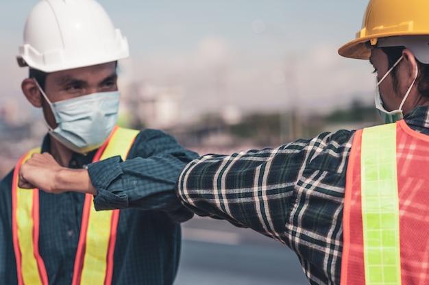Инженер пожимает руку новому нормальному социальному дистанцированию