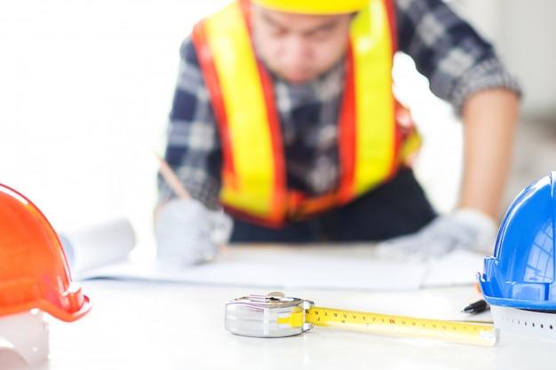 エンジニアが紙を描く上で建設計画をスケッチします。
