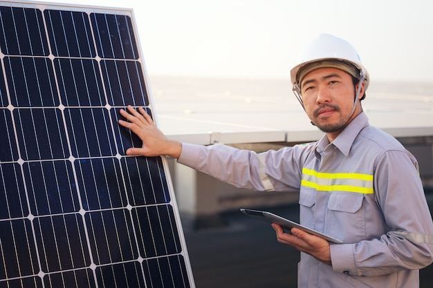 Engineer solar photovoltaic panels station checks with tablet computer. energy technology concept