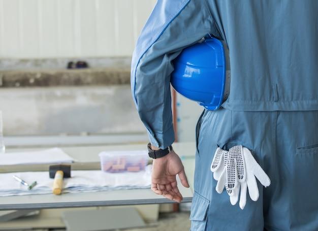 作業の準備ができているポケットに手袋でヘルメットを保持しているエンジニアスタンド
