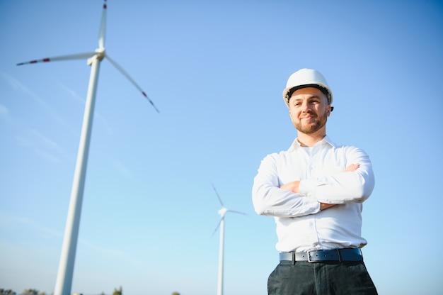 Инженер стоит и держит ноутбук с ветряной турбиной.