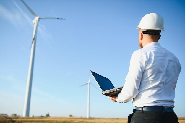 엔지니어가 서서 풍력 터빈이 있는 노트북을 hoding합니다.
