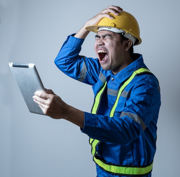 Engineer stressful holding tablet on hand isolated background. engineer having problem in work