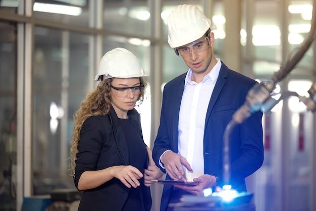 工場で自律製品のプロセス産業ロボットアームを監督するエンジニア