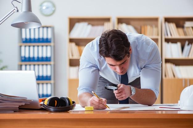 Инженер-супервайзер работает над чертежами в офисе