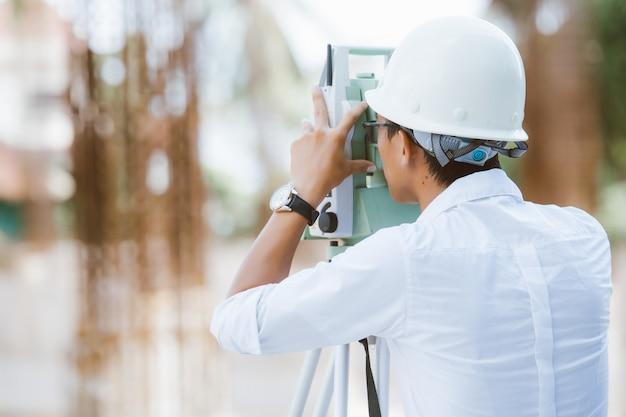 新しい建設プロジェクトでセオドライトを扱うエンジニア測量士