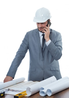 Engineer talking on call phone, smiling at work place, table and many tools nearby.
