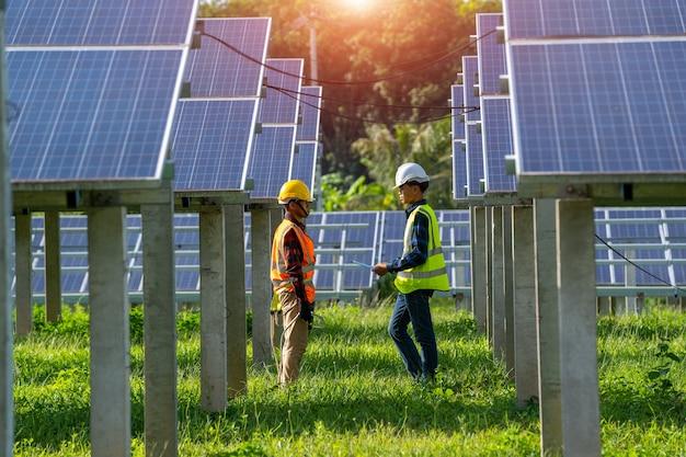 Команда инженеров работает и устанавливает солнечные панели на солнечной электростанции, инновационные решения для решения проблем энергии, использование возобновляемых ресурсов, зеленая энергия.