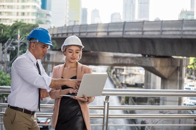 엔지니어 팀워크는 현대 도시의 건설 현장에서 프로젝트 계획을 논의합니다. 젊은 미국 젊은 여성 엔지니어와 고위 보스는 노트북 컴퓨터에서 청사진 계획을 확인합니다.