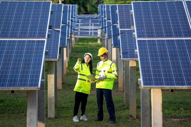 Engineer and technician checking equipment in solar panels.