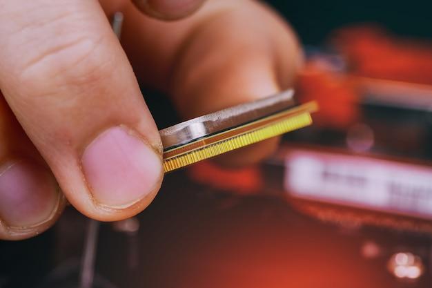 Engineer technician plug in computer cpu microprocessor to motherboard socket.