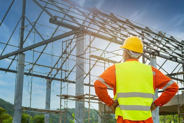 Инженер-техник наблюдает за командой рабочих на высокой стальной платформе,