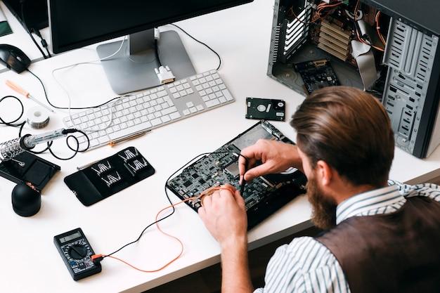 マルチテスターでコンピューター回路をテストするエンジニア。テスターケーブルを手に、分解されたcpuの近くの電子部品を調べている認識できない修理工の上面図