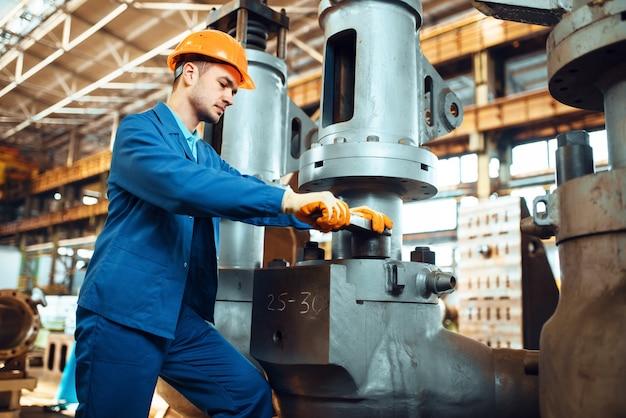 Engineer in uniform and helmet works on factory. industrial production, metalwork engineering, power machines manufacturing