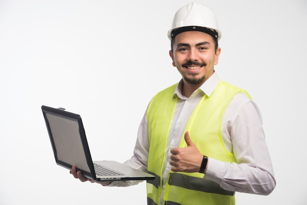 Engineer in uniform holding a laptop and making thumb up.