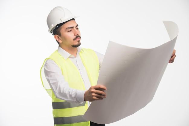 Ingegnere in divisa che tiene e legge il progetto architettonico della costruzione.